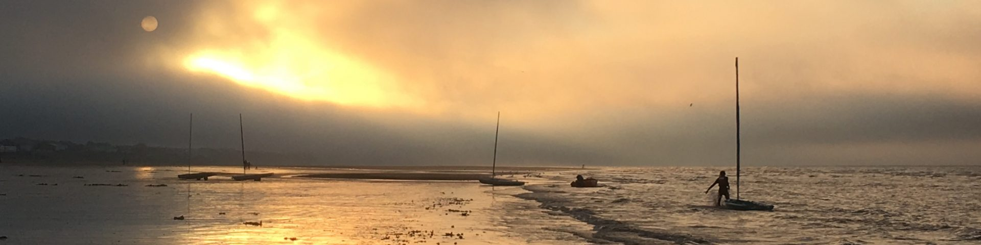 sun setting behind clouds with boats in the foreground